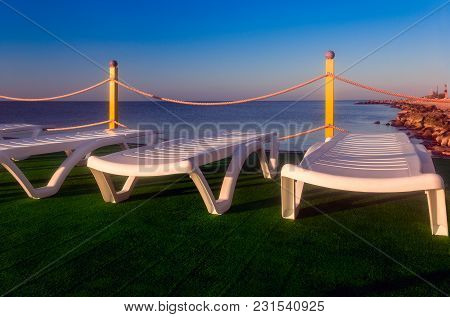 Sunbeds On The Grass By The Sea With Yellow Fence