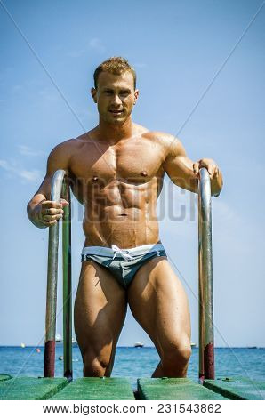Handsome young bodybuilder getting out of sea or ocean water looking at his muscular torso, pecs, arms and abs poster