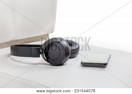 Powerful Wireless Headphones Lying On A White Leather