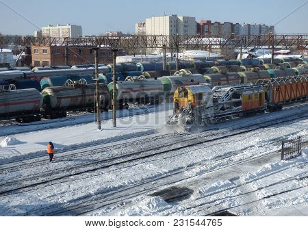 Snow Removal Train Clears Railway At The Station. Lot Of Cargo Cars And Oil Tanks At The Back. Sunny