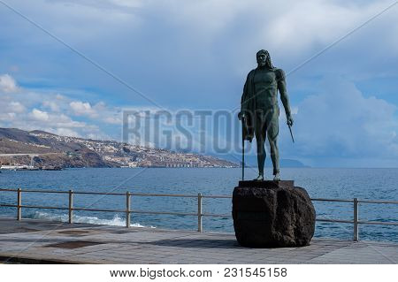 Guanche Sculpture Over Ocean Background In Candelaria On Tenerife Island. Copy Space.