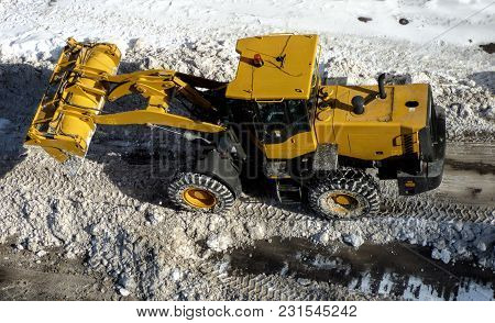 Big Yellow Tractor Cleaning Road. Bulldozer Remove Snow From The Street. Snowplow In City, Sunny Win