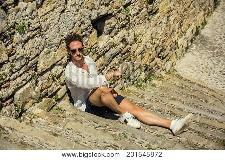 Side View Of Stylish Man In Sunglasses Sittingon Stone Stairs And Relaxing. Ocean On Background.