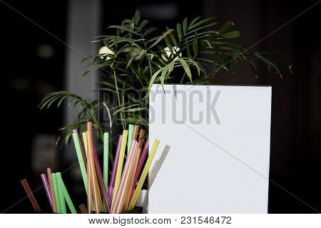 A White Empty Advertising Medium Stands On A Table Next To Colorful Bright Straws And Flower Leaves