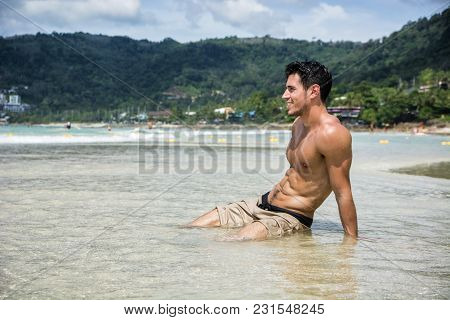 Handsome Young Man Laying Down On A Beach In Phuket Island, Thailand, Shirtless Wearing Boxer Shorts