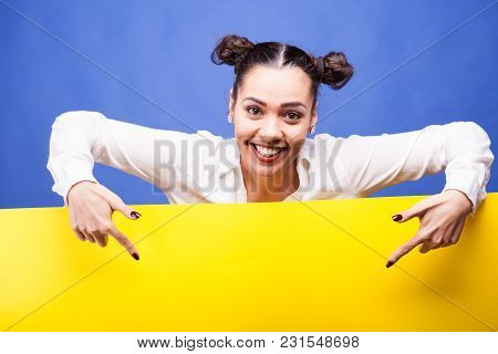Surprised Woman Next To A Yellow Banner Over Blue Background In Studio Photo