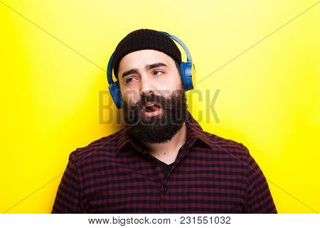 Hipster With A Blue Wireless Headset Listening To Music On Yellow Background