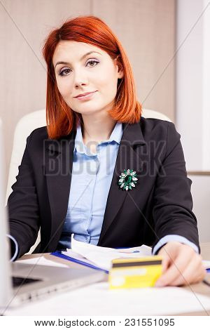 Redhead Businesswoman With A Credit Card In Hands Smiling And Looking At The Camera
