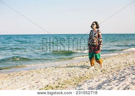 A Girl Is Walking Along The Beach.