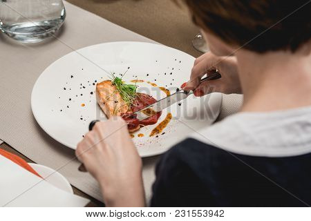 Woman Eats Delicious Salmon In A Restaurant. Small Portion On A White Plate. Food And Wine Tasting