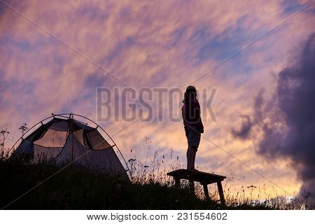 Traveler Girl Near The Tent Looks At Sunrise In Mountains Of Romania. Picture From Below. Girl On Th