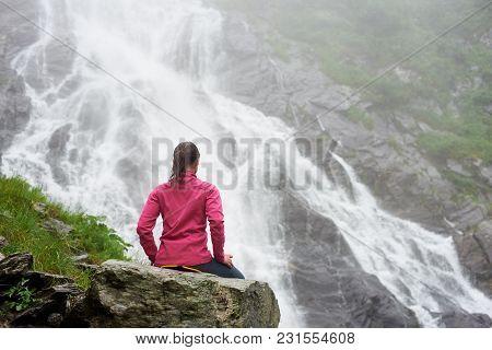 Rearview Shot Of A Female Traveller Sitting Near The Stunning Balea Rocky Waterfall Enjoying The Sce