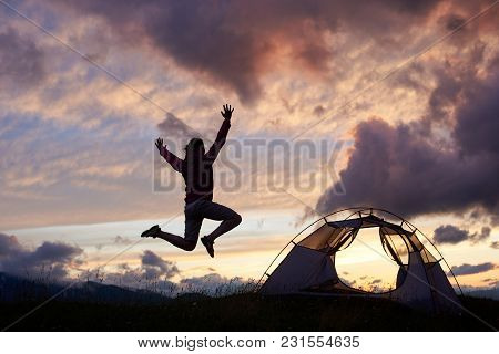 Female Tourist Jumping High Adoring Beautiful Scenery Around On Moutain Hill In Romania. Girl Woman