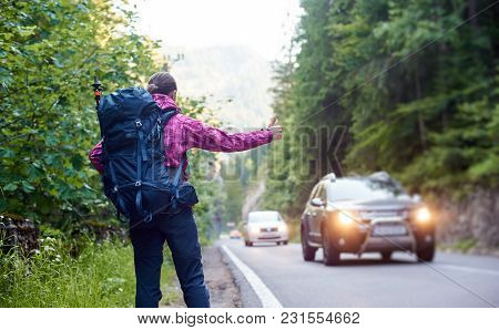 Female Tourist With Backpack Hitchhiking A Car On Mountain Road With Green Rocky Hills And Trees Nea