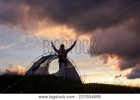Touching The Sky. Female Climber Lifting Hands To Sky Enjoying Amazing Sunset In Mountains In Romani