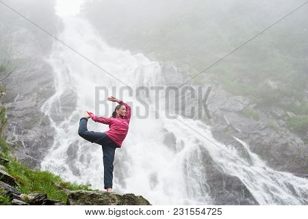 Sporty Girl Posing Under A Waterfall Balea In Fagarash Mountains. Rocky Waterfall In The Mountains.