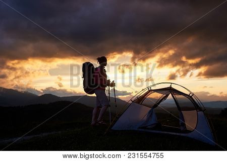 Happy Hiker Woman Standing Near The Tent With Backpack On Her Shoulders And Walking Sticks In Hands