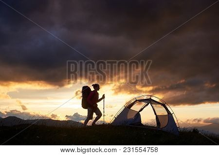 Hiking Girl With Trekking Sticks And A Backpack Hiking Near Tent, Sunset Time With Rising Sun In The