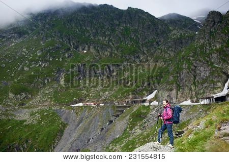 Smiling Hiker Girl With Blue Backpack And Trekking Sticks Standing In A Valley Under Rocky Mountains