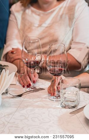 Woman Holds Glass Of Red Wine. A Lot Of Different Wine Glasses On The Table At Wine Tasting. People