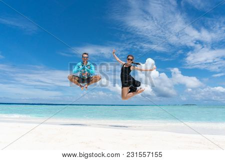 Man And Woman Jump On Beach With Pure Transparent Water Of Ocean In Maldives