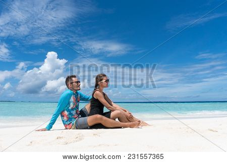 Man And Woman Sit On Beach With Pure Transparent Water Of Ocean In Maldives