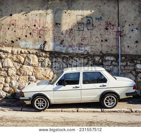 Sarajevo, Bosnia-erzegovina - February, 16: Car Next To The Old War Covered By Gunfire Left Over Fro