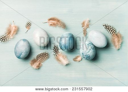 Painted Traditional Eggs For Easter Holiday And Feathers Over Light Blue Background, Top View, Horiz