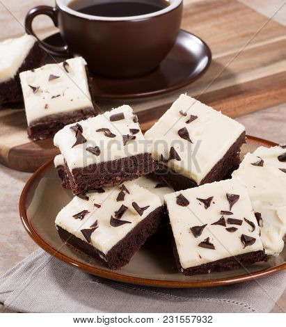 Pile Of Chocolate Fudge Brownies On A Plate With A Cup Of Coffee In Background