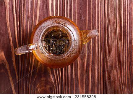 Hot Black Tea In Glass Tea Pot, Overhead On Wooden Table