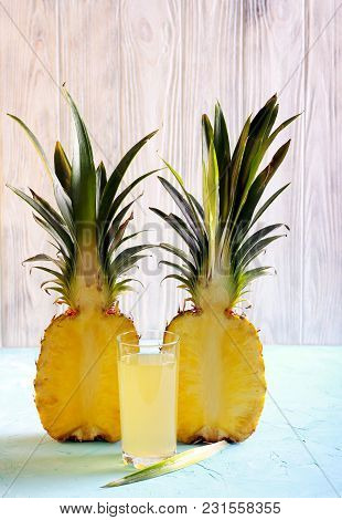 Pineapple Half And Pineapple Juice In A Glass Over Wooden Background
