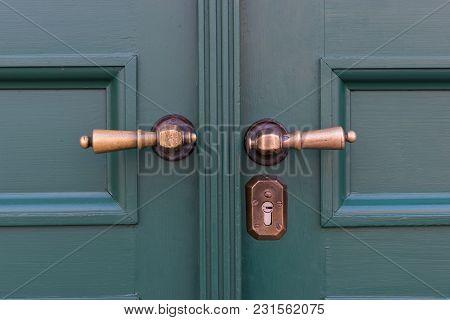 Golden Door Handles On Green Wooden Doors. Old Door Handle