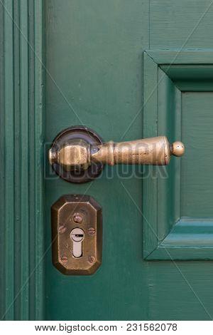Golden Door Handles On Green Wooden Doors. Old Door Handle.