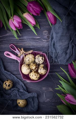 Spotted Quail Eggs And Tulips On A Dark Wooden Background. Rustic Style, Top View