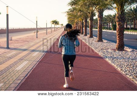 Girl Jogging On The Running Track By The Seaside