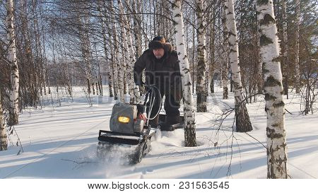 Man In Winter Clothes Fast Riding On Mini Snowmobile On Deep Snowdrifts In The Forest And Maneuverin