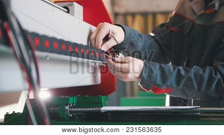 Electrician In Overalls Is Working With Energy Panel And Machinery Equipment On Plant, Close Up