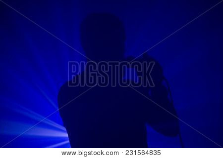 Photo Of Man's Silhouette In Mist Singing To The Microphone With Blue Lights In The Background