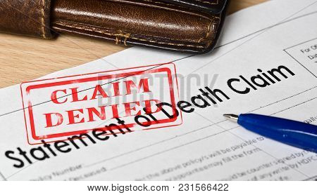 Statement Of Death Claim Form On A Wooden Surface. Next Is A Blue Fountain Pen, Leather Purse. On Th