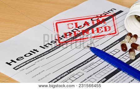Healt Insurance Claim Form On A Wooden Surface. Next Is A Blue Fountain Pen And Pills. On The Form I
