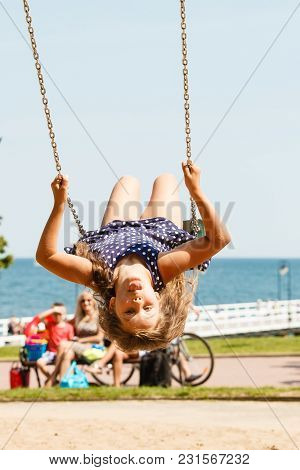 Craziness And Freedom. Young Summer Girl Playing On Swing-set Outdoor. Crazy Playful Child Swinging