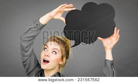Shocked Student Looking Woman Wearing Grey Shirt Holding Black Thinking Bubble, Gray Background.