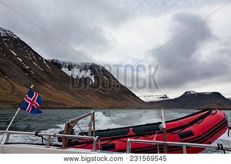 Icelandic Flag And Rubber Boat Sailing In A Fjord With Mountains Background, Iceland