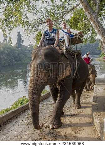 Kanchanaburi,thailand- February 20,2018: Tourists Ride Elephants By The River, To The Place Of Bathi