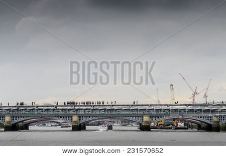 Unidentifiable Pedestrians Cross The Millennium Bridge In London, England, Uk With Other London Brid