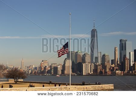 Ellis Island, New York - Feb 28, 2018: The Us Flag Flies At Half Staff With New York City As A Backd