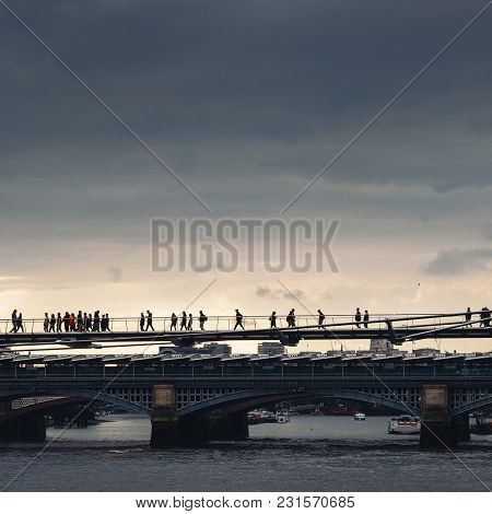 Backlit Silhouette Of Unidentifiable Pedestrians On The Millennium Bridge In London, England, Uk