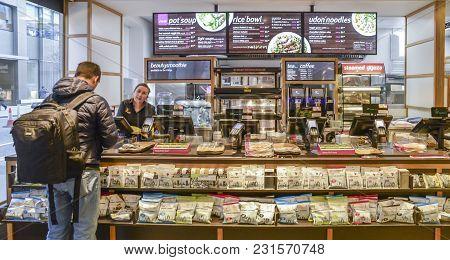 London, Uk- Mar 13, 2018: Customer At Counter Paying For Food At Itsu Health And Happiness Restauran