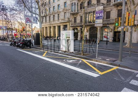 Barcelona, Spain. February 2018: Charging Station In Barcelona, Passeig De Gracia, And Sign On The S