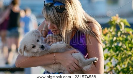 Young Girl Holding 3 Month Old Labrador Retriever Puppy, Outdoor